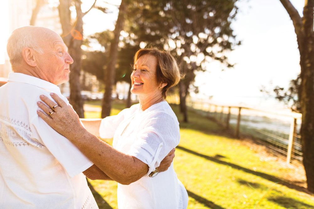 Charter Senior Living Residents couple dressed all in white smiles and dances together outdoors