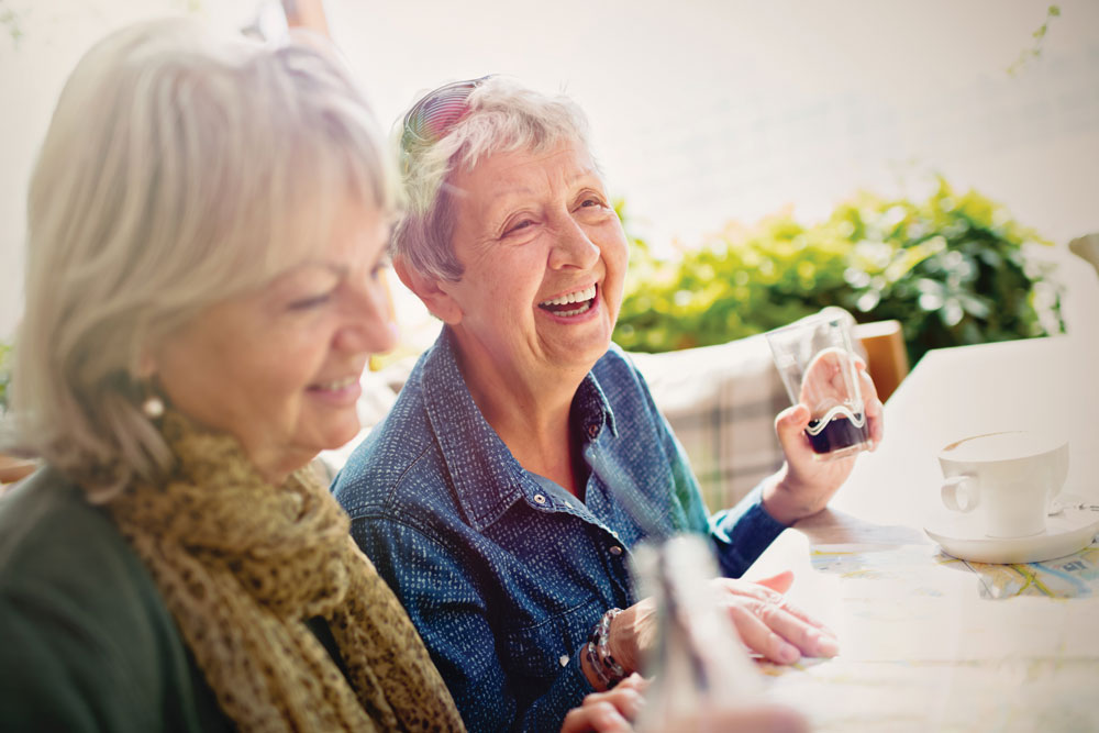 Two female residents of Charter Senior Living at Bowling Green smile and share beverages while sitting at an outdoor table