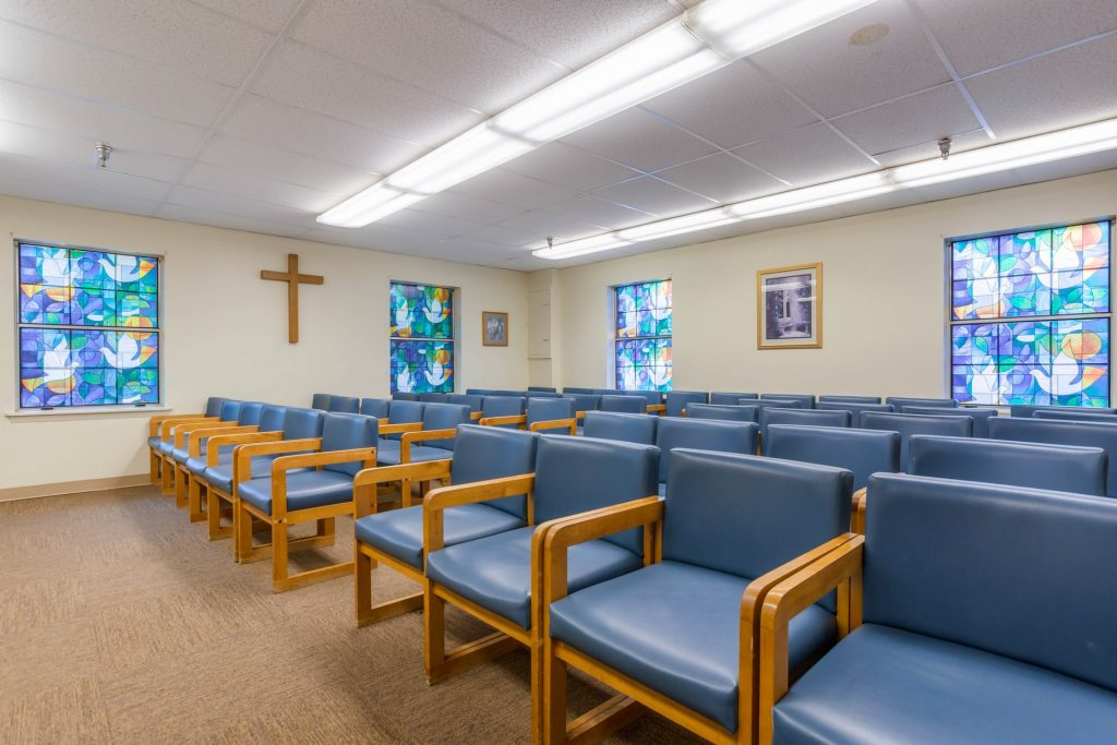 Chapel with several rows of chairs, stained glass windows, and a cross on the wall
