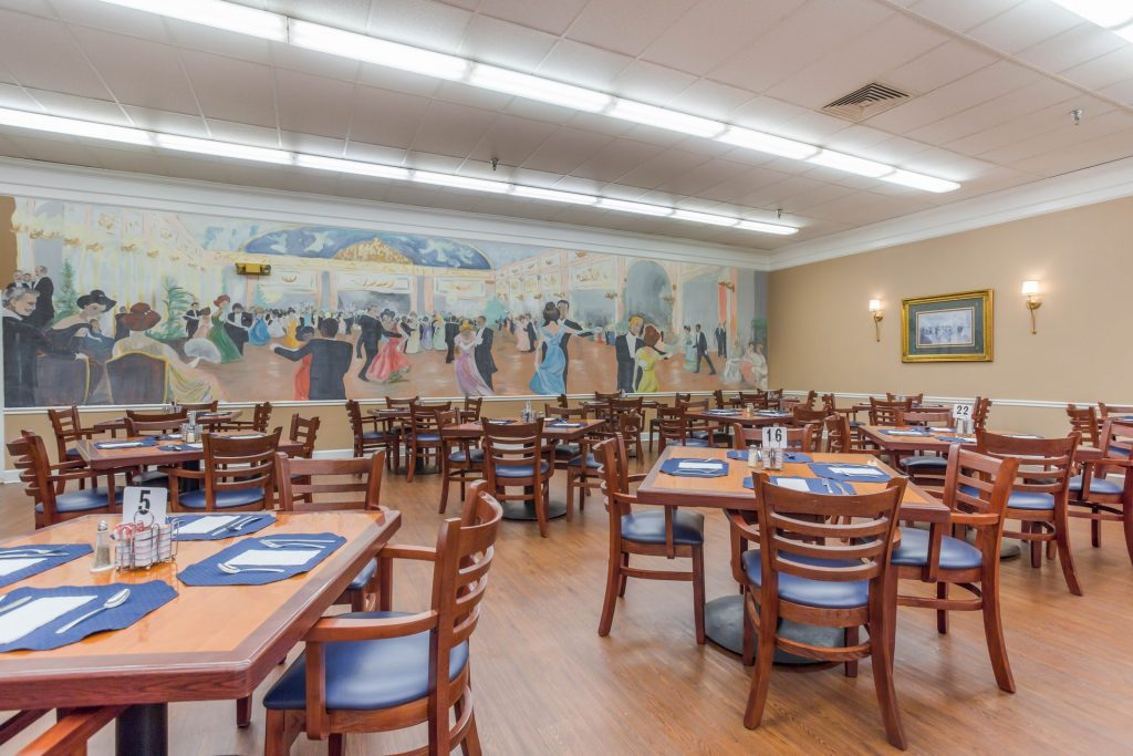 Large dining room filled with tables and chairs featuring a mural of ballroom dancers on the wall