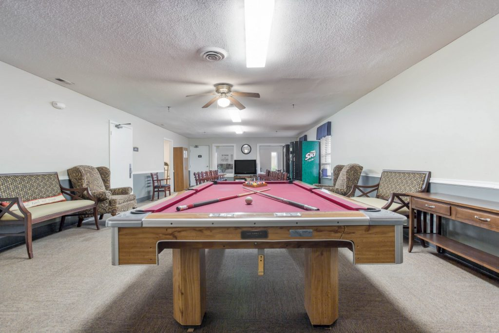 Game room featuring pool table and numerous armchairs, benches, and vending machines