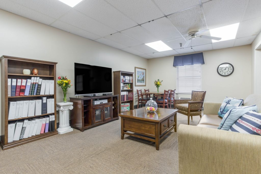 Sitting area featuring sofa, television, bookshelf, coffee table, table and chairs set, and various decor