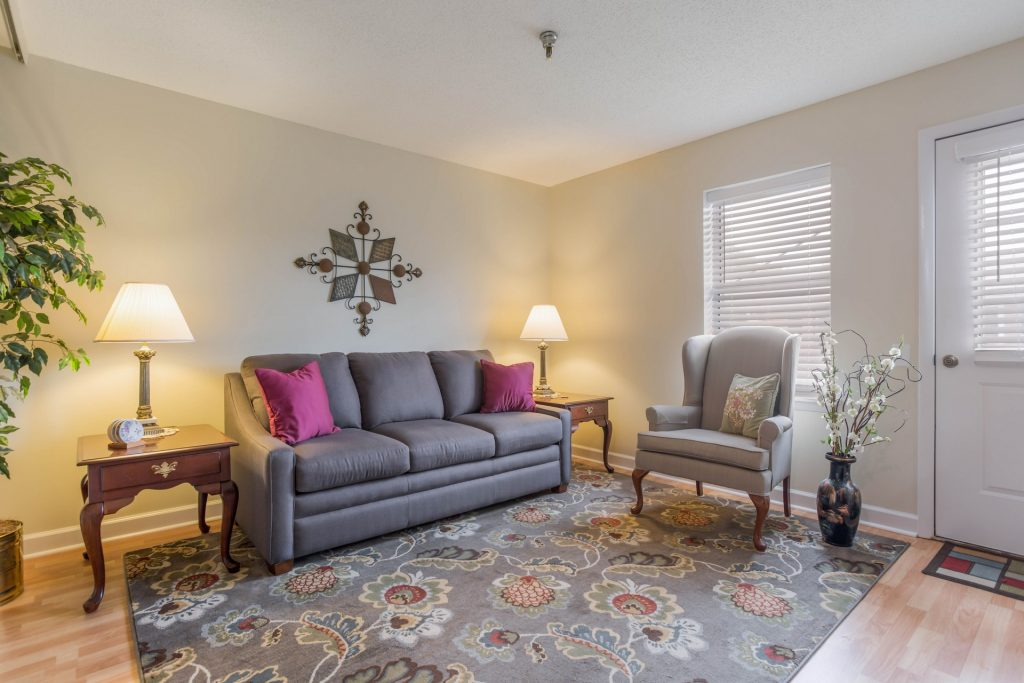 Living area with sofa, chair, rug, window, lamp, various decorations, and door to the outside