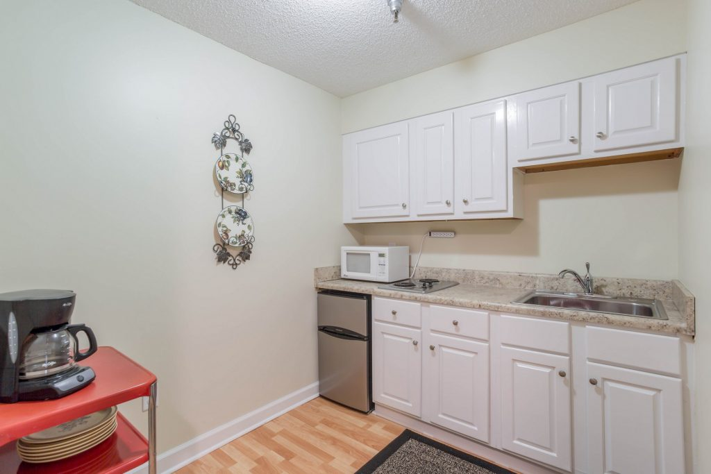 Neutral-toned kitchen area with white cabinets, a fridge, coffee maker, microwave, sink, and hot plate