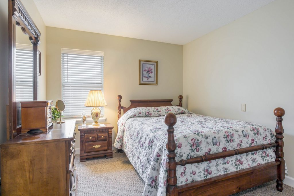 Bedroom with bed, sidetable, dresser, window, lamp, and painting