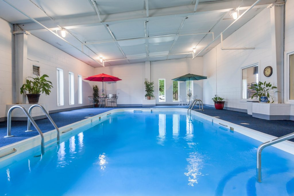 Indoor swimming pool with several tables and chairs in the lounge area and various plants