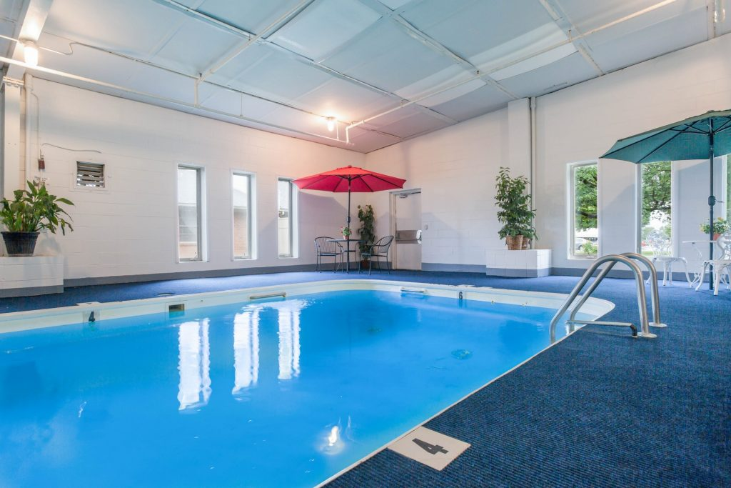 Side view of indoor swimming pool, tables and chairs area, and multiple floor-to-ceiling windows
