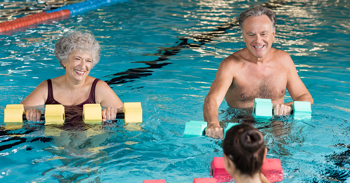 senior mean and women exercising in a pool